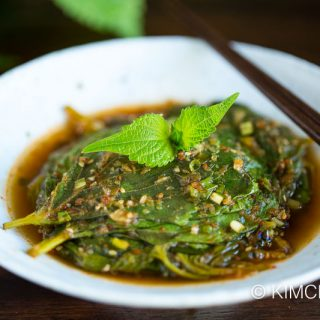 steamed perilla leaves plated on white dish with chopsticks