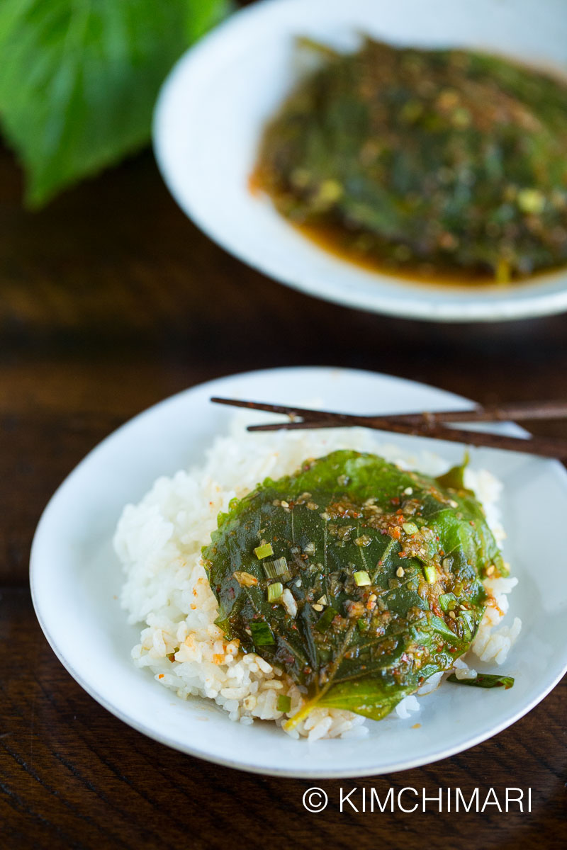 steamed perilla leaves laid out on a bowl of rice with chopsticks