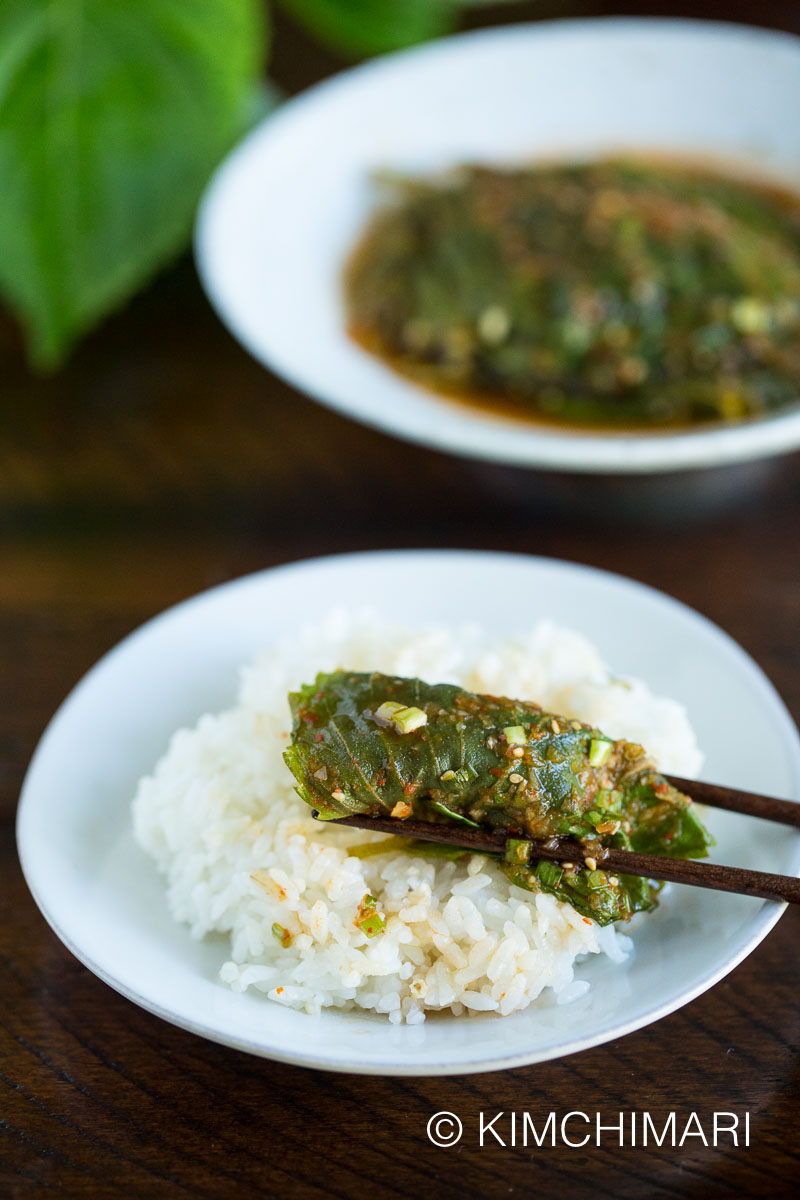 steamed perilla leaf on white rice wrapped around with chopsticks