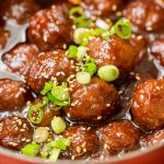 gochujang meatballs finished in pot topped with green onions and sesame