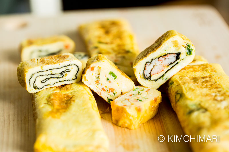 3 different egg roll variations of seaweed, carrots and ham and crabmeat cut into slices on cutting board