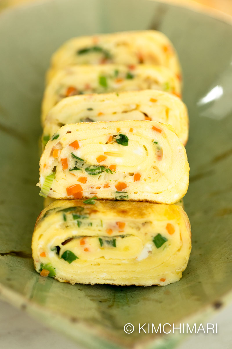 korean egg roll with carrots, ham and green onion cut into slices and plated on green dish