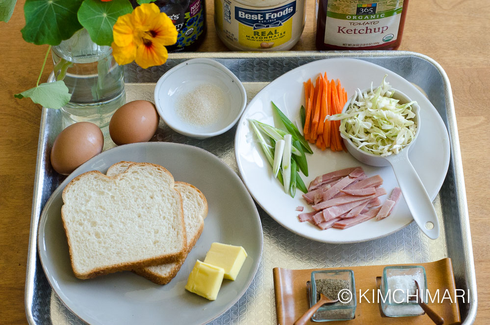 eggs, bread, butter, cut vegetables, salt pepper all laid out on a tray