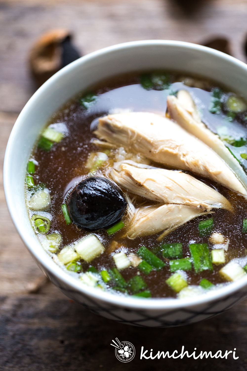 Korean Chicken soup with torn meats in bowl with Black Garlic and green onions