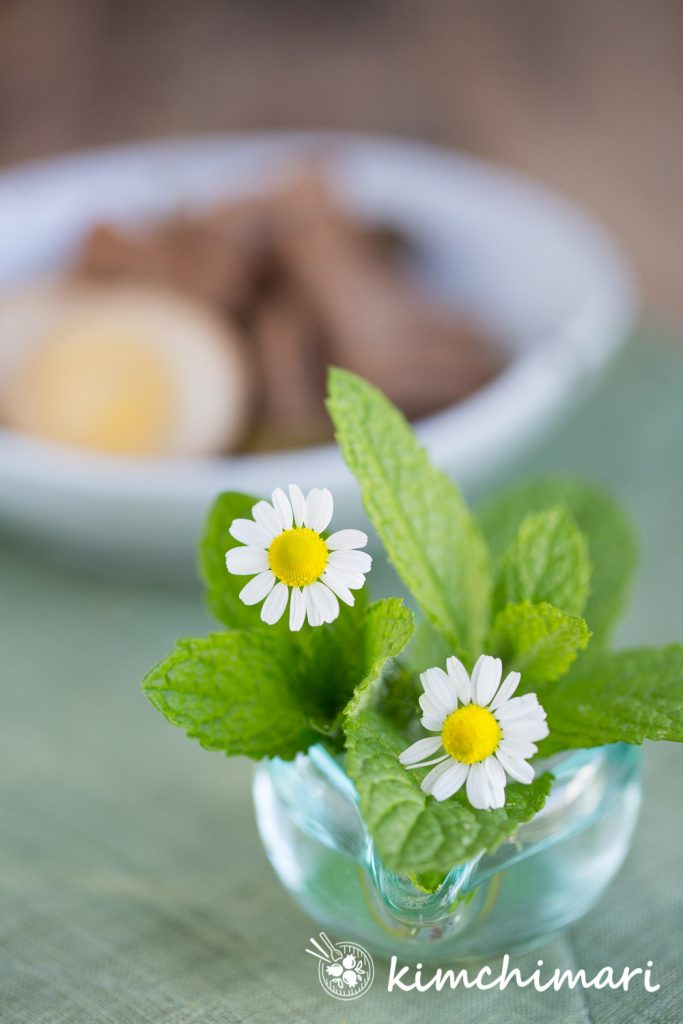 chamomile flowers mint in small glass bowl with jangjorim plated in the background
