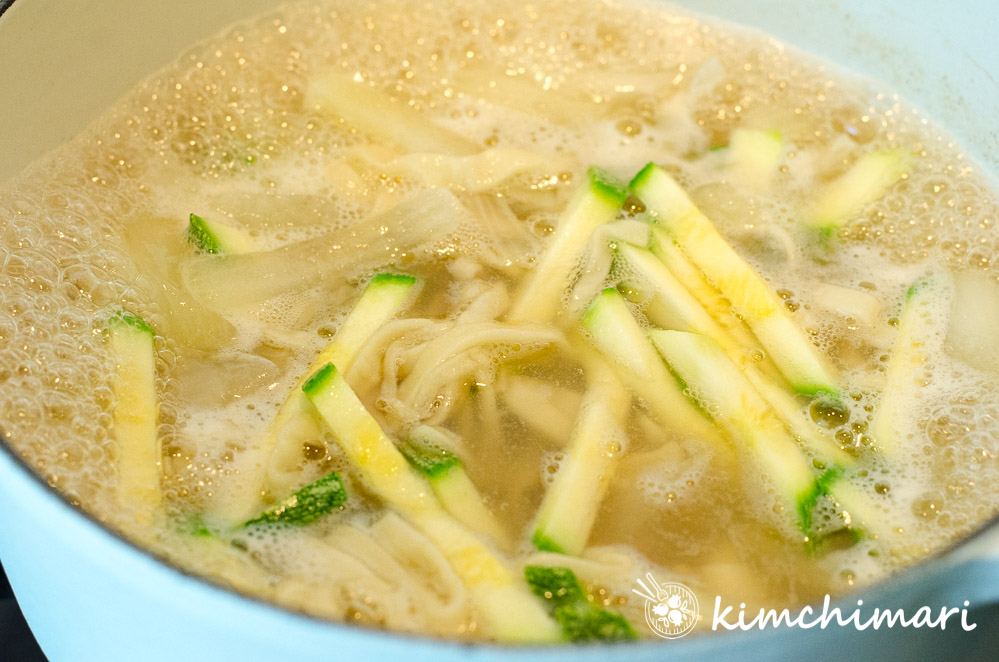 noodles and zucchini cooking in broth in pot