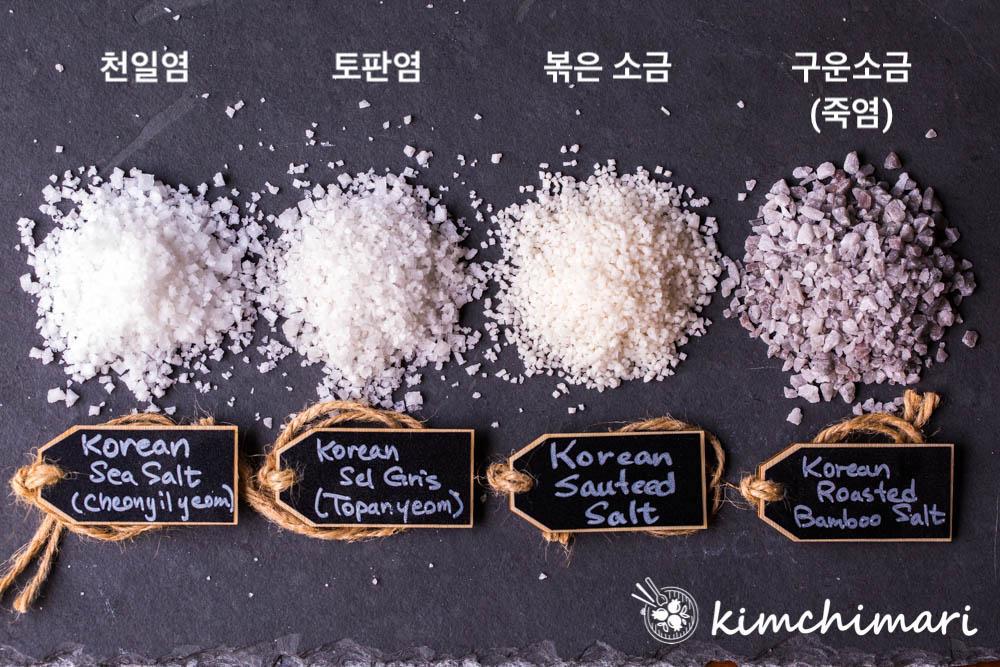 4 different korean salts laid on small piles on black slate