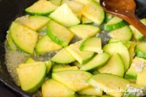 stir-frying seasoned zucchini in frying pan