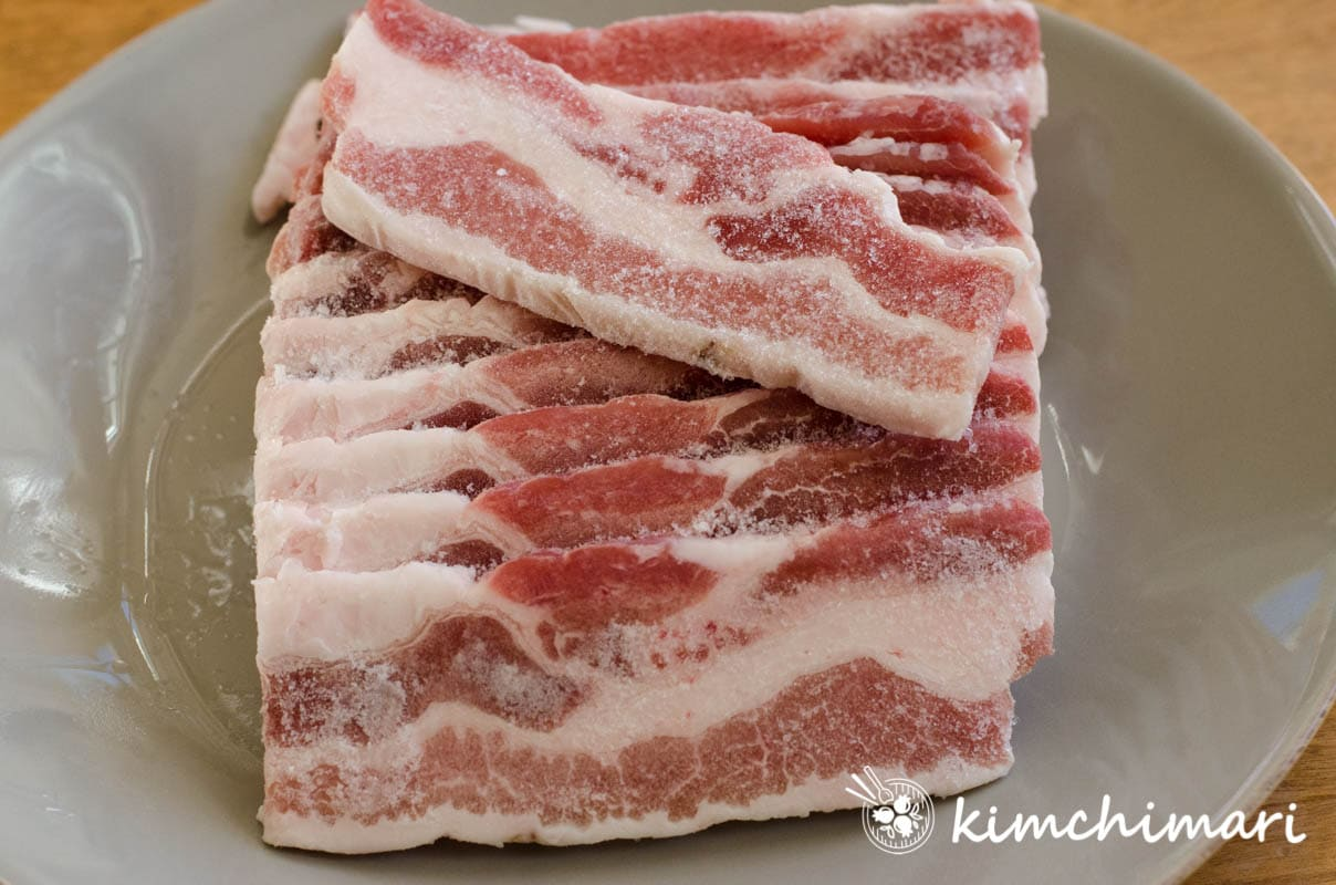 pork belly slices partially frozen on grey plate