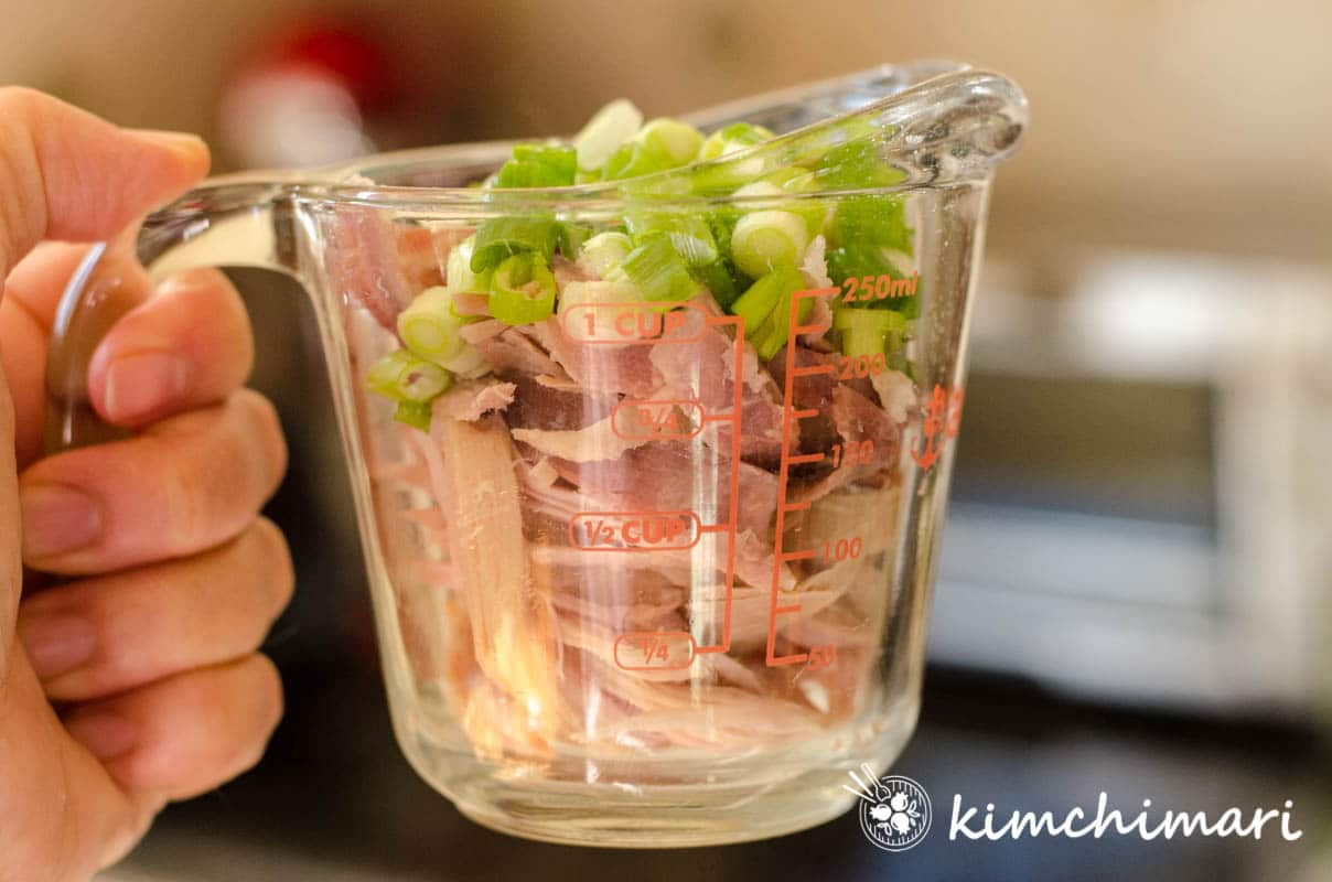 shredded turkey in glass measuring cup topped with green onions