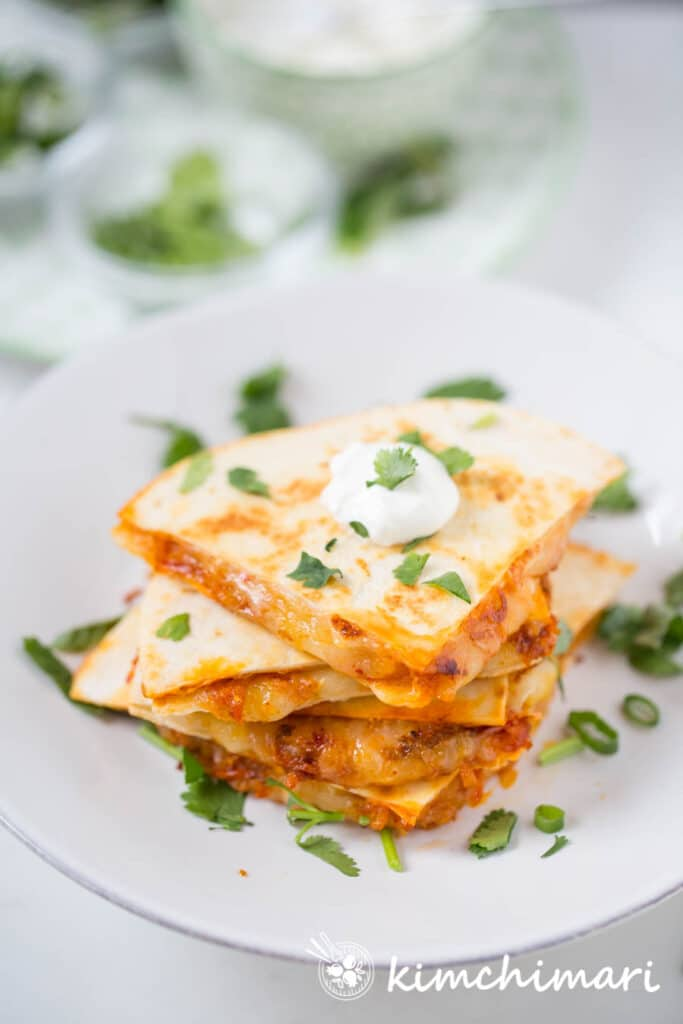 top view of sliced quesadillas on white plate with herbs sprinkled on top