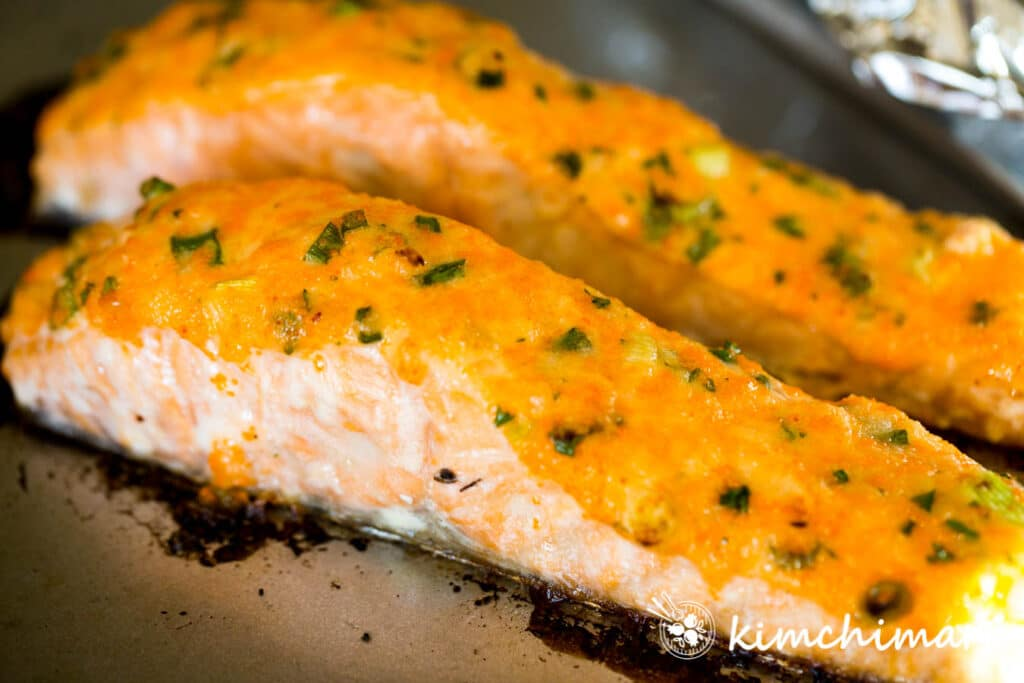 baked salmon covered in mayo sauce on sheet pan