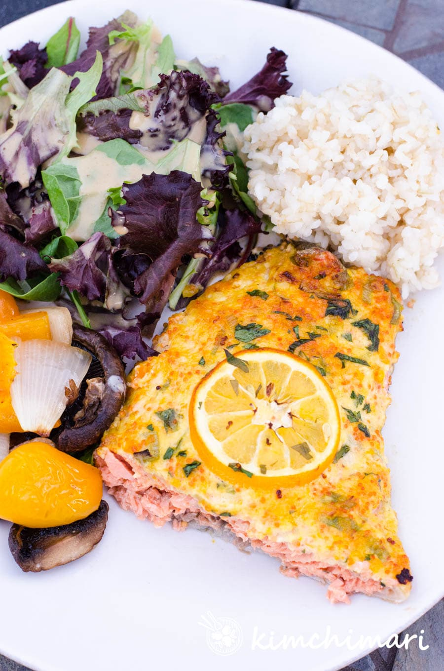 a plate of rice, salmon, salad and grilled vegetables