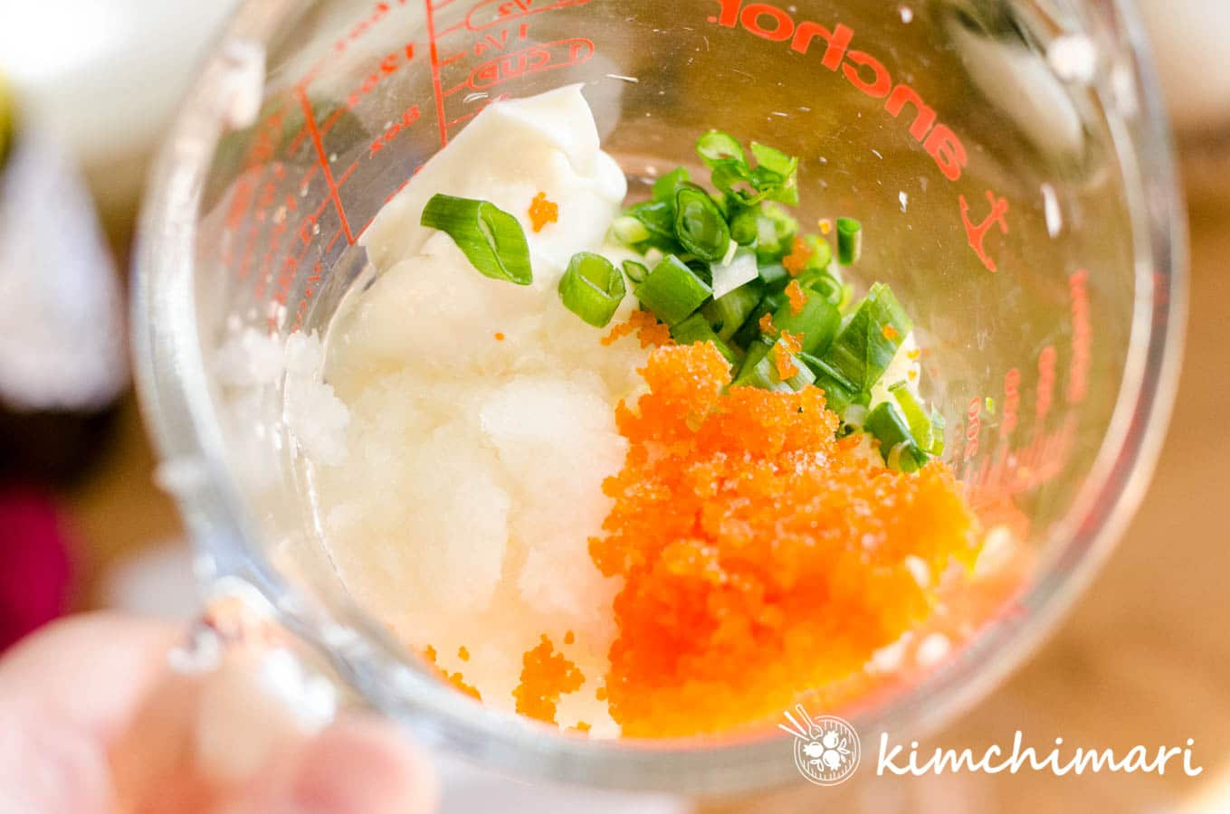 mayo masago onions are in a glass pyrex mixing cup