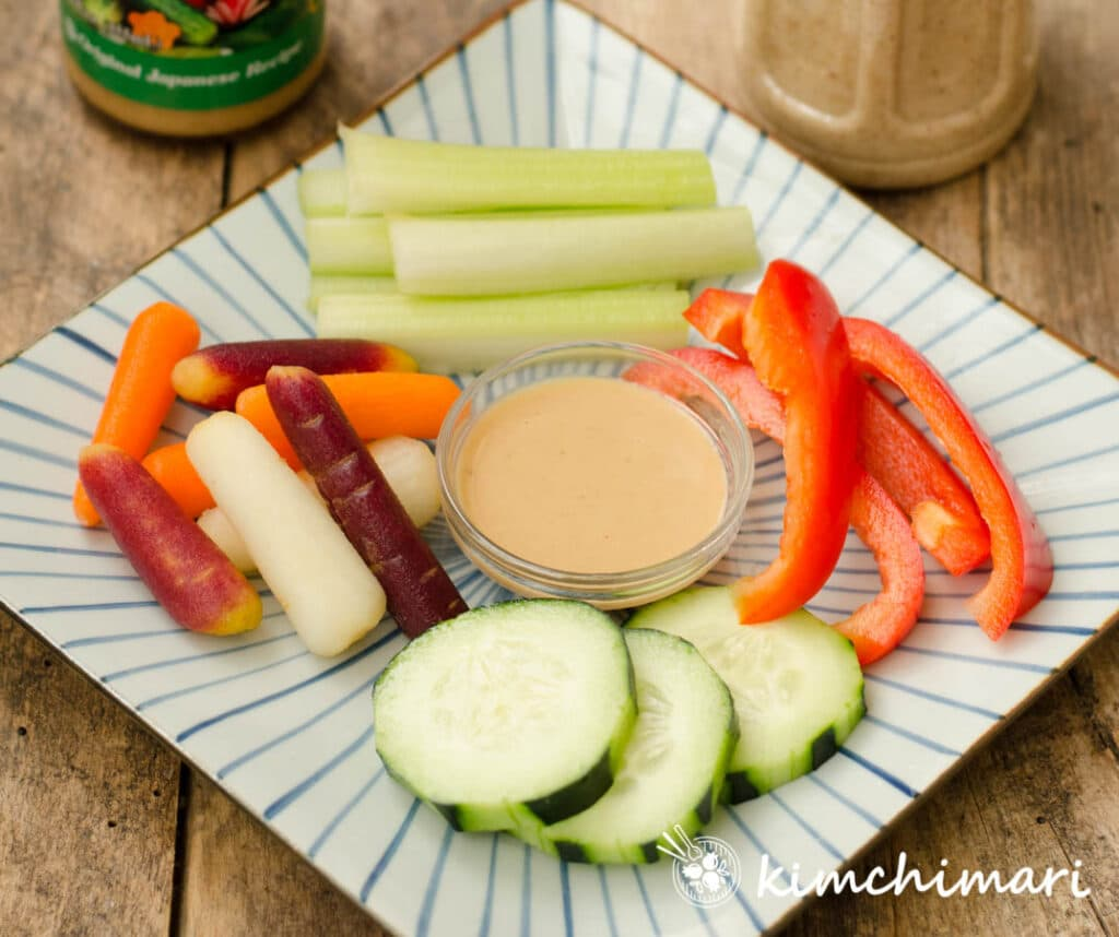 celery, carrots, bell peppers, cucumbers cut into sticks and served with salad dressing on square plate